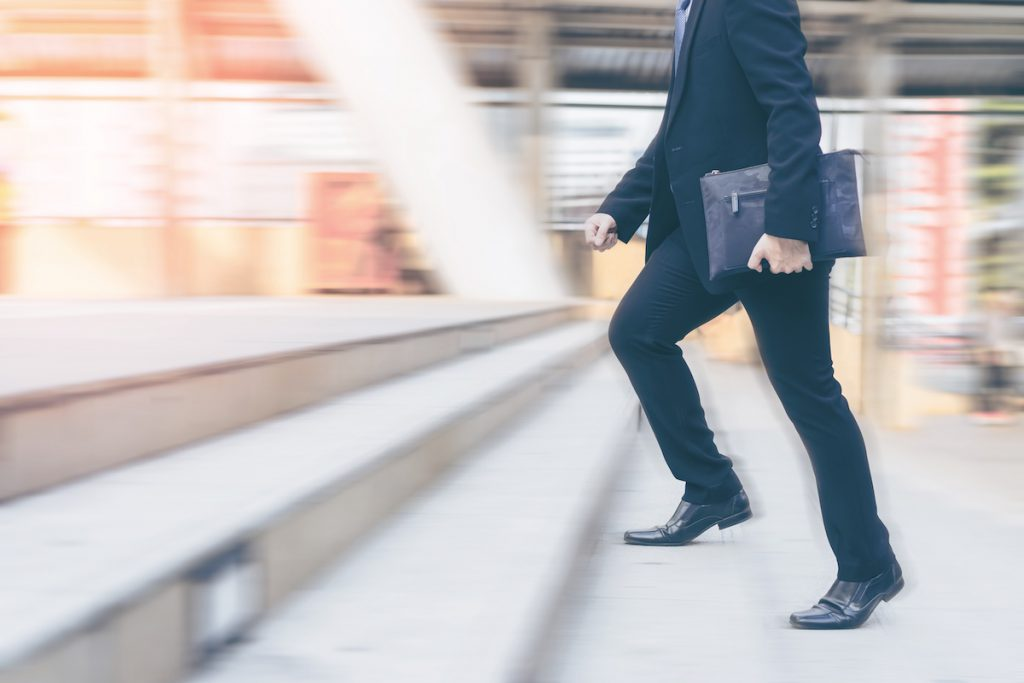 family office employee walking up stairs with briefcase